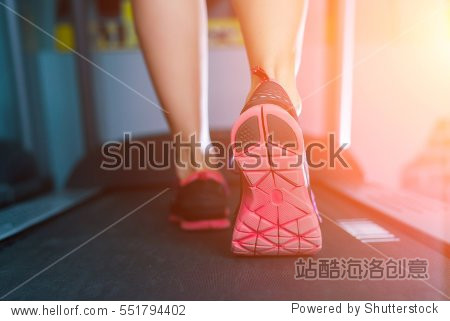 Female muscular feet in sneakers running on the treadmill at the gym