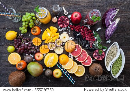Fruits and frozen berries on dark rustic wooden table. Purple and yellow smoothie bowl formula. Clean eating concept. Various green and red veggies, fruit and superfoods ready to prepare smoothie bowl