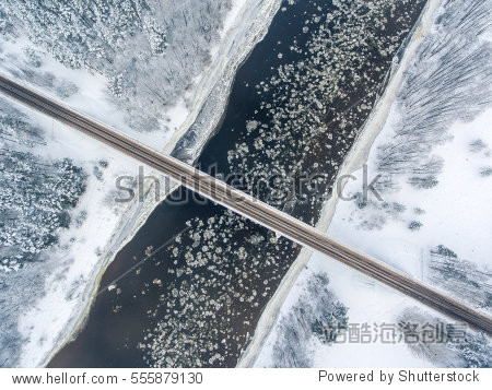 Winter season aerial top down view of a bridge with a straight line road over river Nemunas.