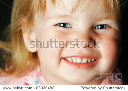 漂亮的蓝眼睛的小女孩微笑的画像特写