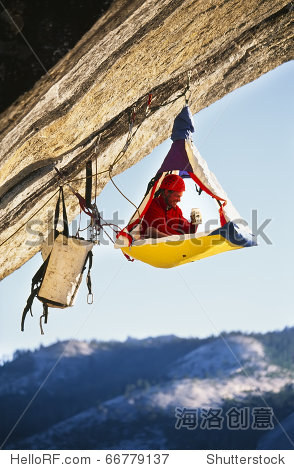 climberplant_rock climber bivouacked in his portaledge on an overhanging clif