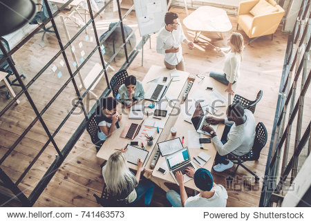 Multiracial young creative people in modern office. Group of young business people are working together with laptop  tablet  smart phone  notebook. Successful hipster team in coworking. Freelancers