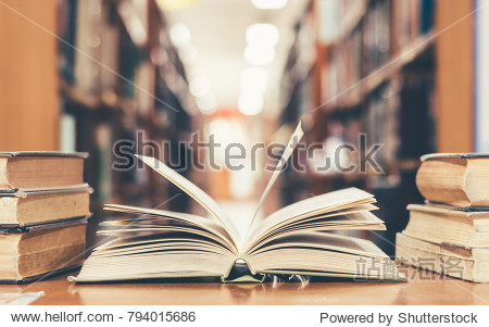 Education learning concept with opening book or textbook in old library  stack piles of literature text academic archive on reading desk and aisle of bookshelves in school study class room background