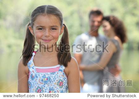 一个小女孩和她的父母在公园里.图片