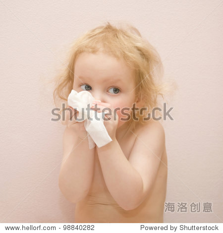 可爱的蓝眼睛的金色卷发小女孩生病了.她有流鼻涕.