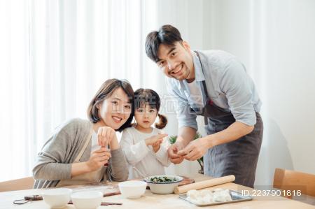 爸爸妈妈和女儿在家包饺子