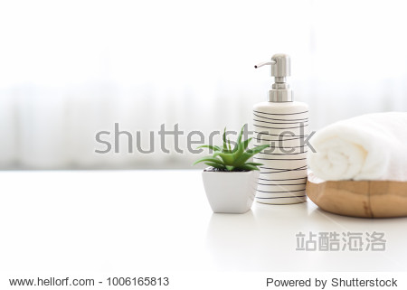 Ceramic soap  shampoo bottles and white cotton towels on white counter table inside a bright bathroom background.
