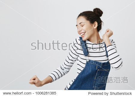 Portrait of brunette Caucasian hipster girl dancing against gray blank wall with smile  rejoicing good mood. Student female with hairbuns having fun while dancing to some pleasant music indoors