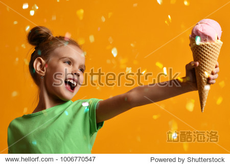Pretty baby girl kid give away vanilla ice cream in waffles cone laughing and smiling on yellow background