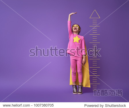 Little child is playing superhero. Kid is measuring the growth on the background of bright ultraviolet wall. Girl power concept. Yellow  pink and  purple colors.