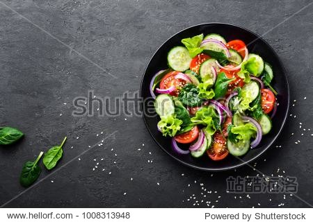 Healthy vegetable salad of fresh tomato  cucumber  onion  spinach  lettuce and sesame on plate. Diet menu. Top view.