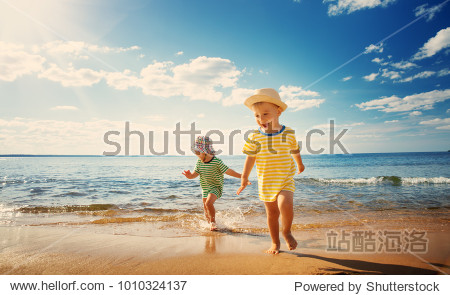 Boy and girl playing on the beach on summer holidays. Children in nature with beautiful sea  sand and blue sky. Happy kids on vacations at seaside running in the water