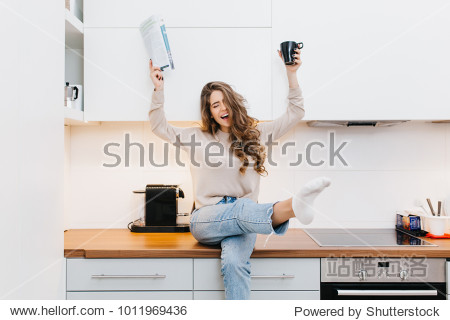 Graceful caucasian girl wears jeans enjoying good morning in her kitchen. Indoor portrait of emotional female model drinking coffee and reading magazine.