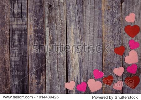 Heart shaped confetti on vintage wooden background. Flat lay  top view.