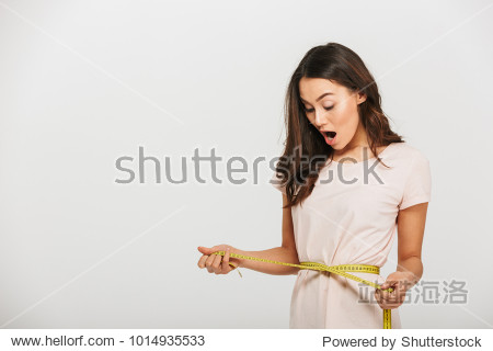 Portrait of a surprised young asian woman holding measuring tape around her waist over white background