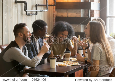 Multiracial happy young people eating pizza in pizzeria  black and white cheerful mates laughing enjoying meal having fun sitting together at restaurant table  diverse friends share lunch at meeting