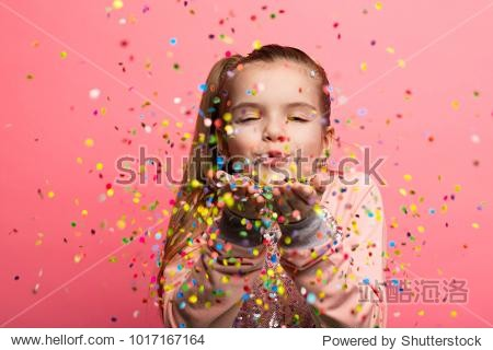 Happy girl celebrating on a pink background. Blows up multicolored confetti