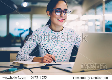 Smart young woman satisfied with learning language during online courses using netbook  smiling female student doing homework task in college library searching information via laptop computer