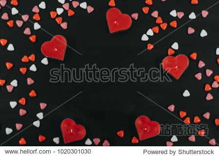 burning hearts shaped candles over black background. Web banner for Valentine's Day. Top view on composition with herts candles and candles. Candy in the form of heart on black background