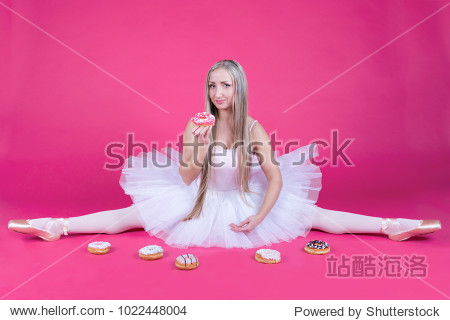 Pretty blonde ballerina in tutu skirt doing a split and eating a donut on pink backdrop.