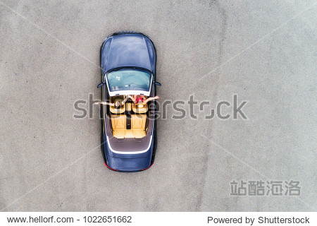 Small passenger sports convertible car with soft top down and happy couple of young women enjoying lifestyle and freedom in aerial top down view.