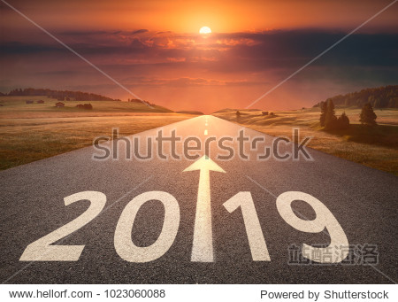 Driving on idyllic open road against the setting sun forward to new year 2019. Concept for success and future.