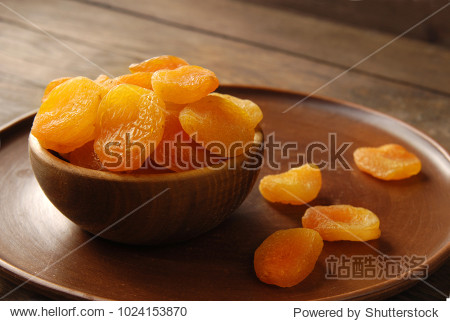 Dried apricots in a bowl on a wooden background.