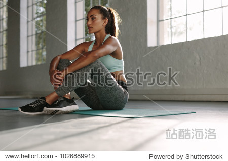 Healthy young female sitting relaxed on yoga mat after training in gym. Woman resting after workout at gym.