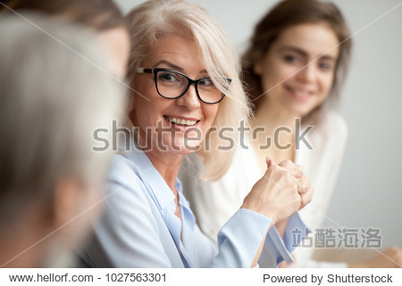 Smiling aged businesswoman in glasses looking at colleague at team meeting  happy attentive female team leader listening to new project idea  coach mentor teacher excited by interesting discussion