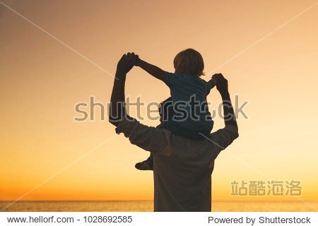 Father and son silhouettes at sunset sky. Loving family and summer vacation. Man and kid boy playing together outdoors on a sea beach. Dad carrying child on his back with raised arms up on nature.