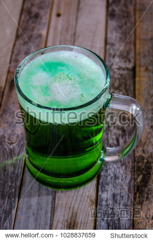 Single mug of green beer on wooden background. Tabletop  side view.