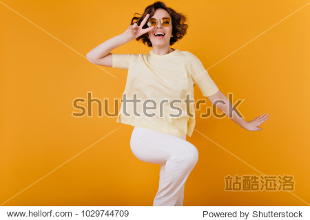 Winsome short-haired girl in white attire dancing on orange background. Studio photo of gorgeous female model fooling around and laughing.