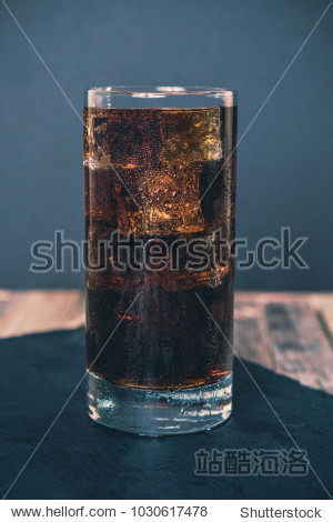 Glass of ice cold cola on dark background