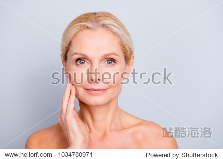 Portrait of pretty  attractive  charming  naked  nude woman touching her  perfect skin  isolated on grey background   after peeling  lotion  mask  perfection  wellness  wellbeing  hydration concept