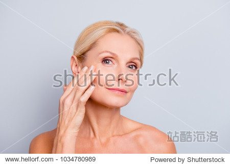 Pretty  charming  attractive woman touching  enjoying her perfect face skin  holding fingers on cheek  pimple  whelk  pustule  dry  oiled  problem skin concept  isolated on grey background
