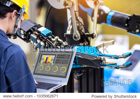 Industry 4.0 Robot concept .Engineers use laptop computers for machine maintenance  automation tools  robot arm at the factory.