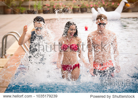 Group of Friends in Swimsuit and Bikini Enjoy Water Splashing in Swimming Pool in the Party on Holiday Summer - Recreation and Lifestyle Concept (ฺBlurry from Movement)
