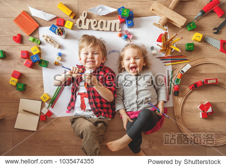 Kids drawing on floor on paper. Preschool boy and girl play on floor with educational toys - blocks  train  railroad  plane. Toys for preschool and kindergarten. Children at home or daycare. Top view