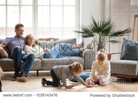 Children sister and brother playing drawing together on floor while young parents relaxing at home on sofa  little boy girl having fun  friendship between siblings  family leisure time in living room