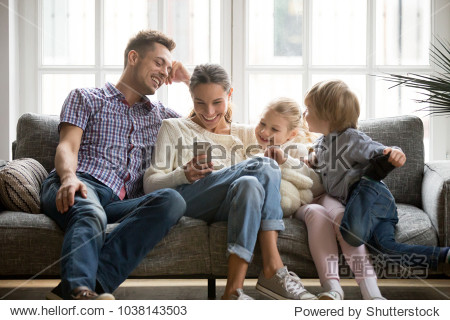 Cheerful young family with kids laughing watching funny video on smartphone sitting on couch together  parents with children enjoying playing games or entertaining using mobile apps on phone at home