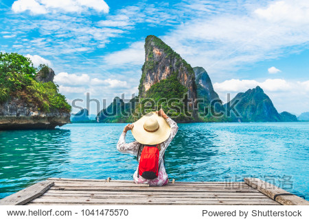 Traveler woman with backpack joy relaxing on floating wood bridge and looking Beautiful destination island  Panyee island  Phang nga bay  Travel Thailand  natural landscape Asia  Summer vacation trip