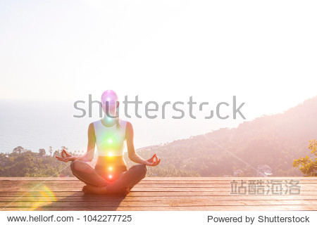 Beautiful woman sits in a pose of a half lotus on high place amazing view of the island outside  she practicing yoga meditation glowing seven all chakra eyes closed calm. Kundalini energy