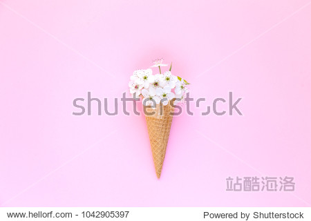 Fashion food set of Ice cream cone with white flowers on top over a pink background  minimalistic design. Top view