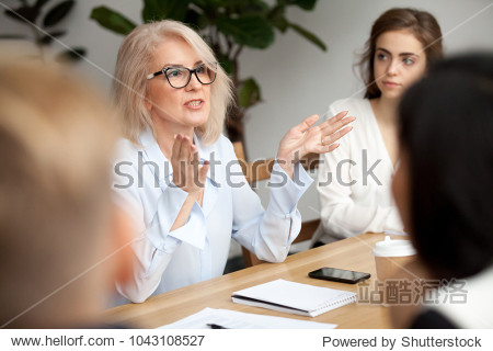 Attractive aged businesswoman  teacher or mentor coach speaking to young people  senior woman in glasses teaching audience at training seminar  female business leader speaker talking at meeting