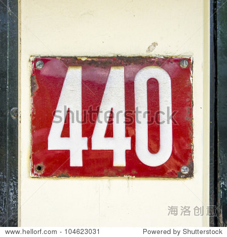 enameled house number four hundred and forty. White lettering on a red background