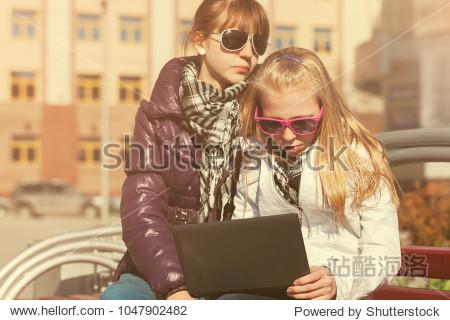 School girls using laptop on the bench in city street