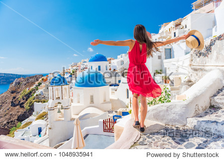 Europe travel vacation fun summer woman dancing in freedom with arms up happy in Oia  Santorini  Greece island. Carefree girl tourist in European destination wearing red fashion dress.