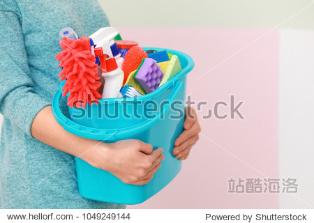 Woman holding bucket with cleaning supplies on color background