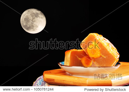 White lotus seed paste mooncake with egg yolk over moon background
