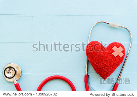 World health day  Healthcare and medical concept. Woman hand holding red heart with Stethoscope  notepad  thermometer and yellow Pill on Pastel white and blue wooden table background texture.